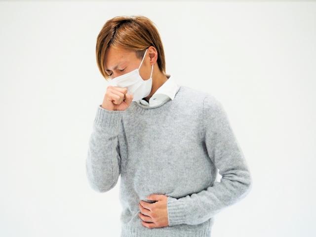 マスクをして咳込む風邪を引いた若い男性