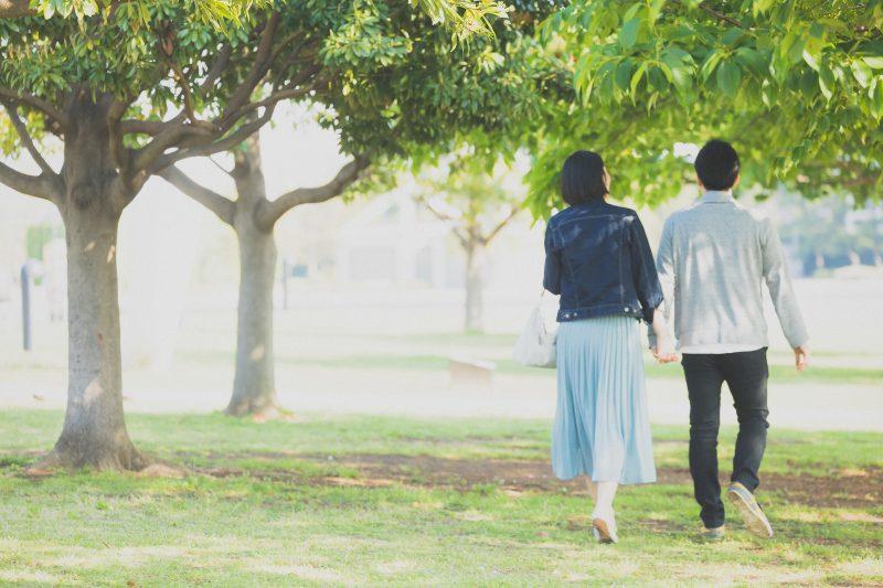 新緑の公園を手をつなぎ歩く夫婦 デート